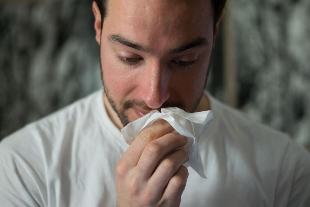 Bearded man daintily dabs at his nose with a tissue — credit to Brittany Colette from Unsplash