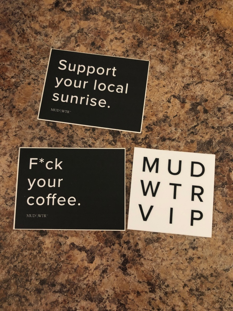 "Stickers from MUD/WTR that read ""support your local sunrise,"" ""f*ck your coffee,"" and ""MUD WTR VIP."""
