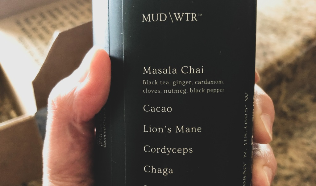 Hand holding a can of MUD/WTR with list of ingredients shown.