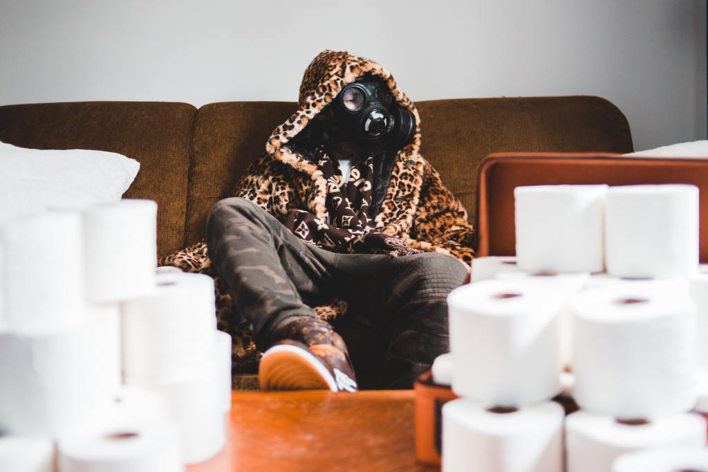 Person wearing gas mask sits on couch surrounded by toilet paper.