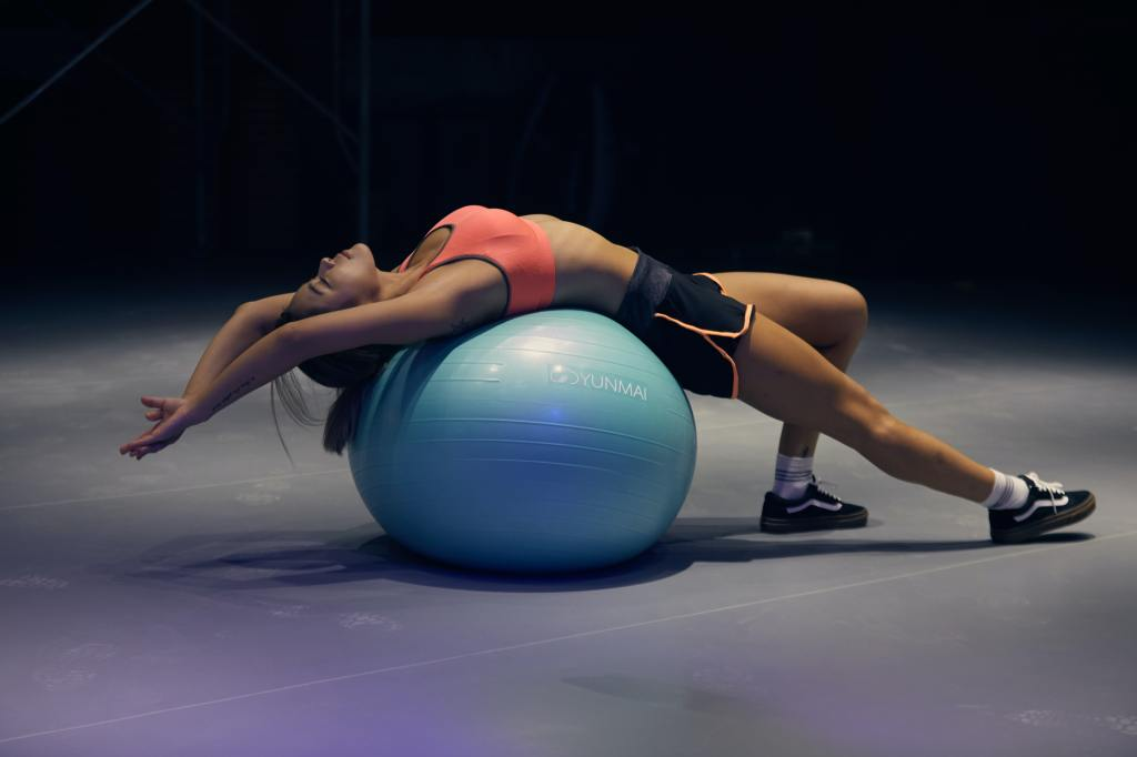 Woman lying on a balance ball