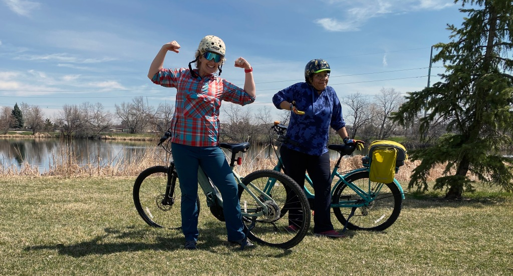 two women pose with e-bikes