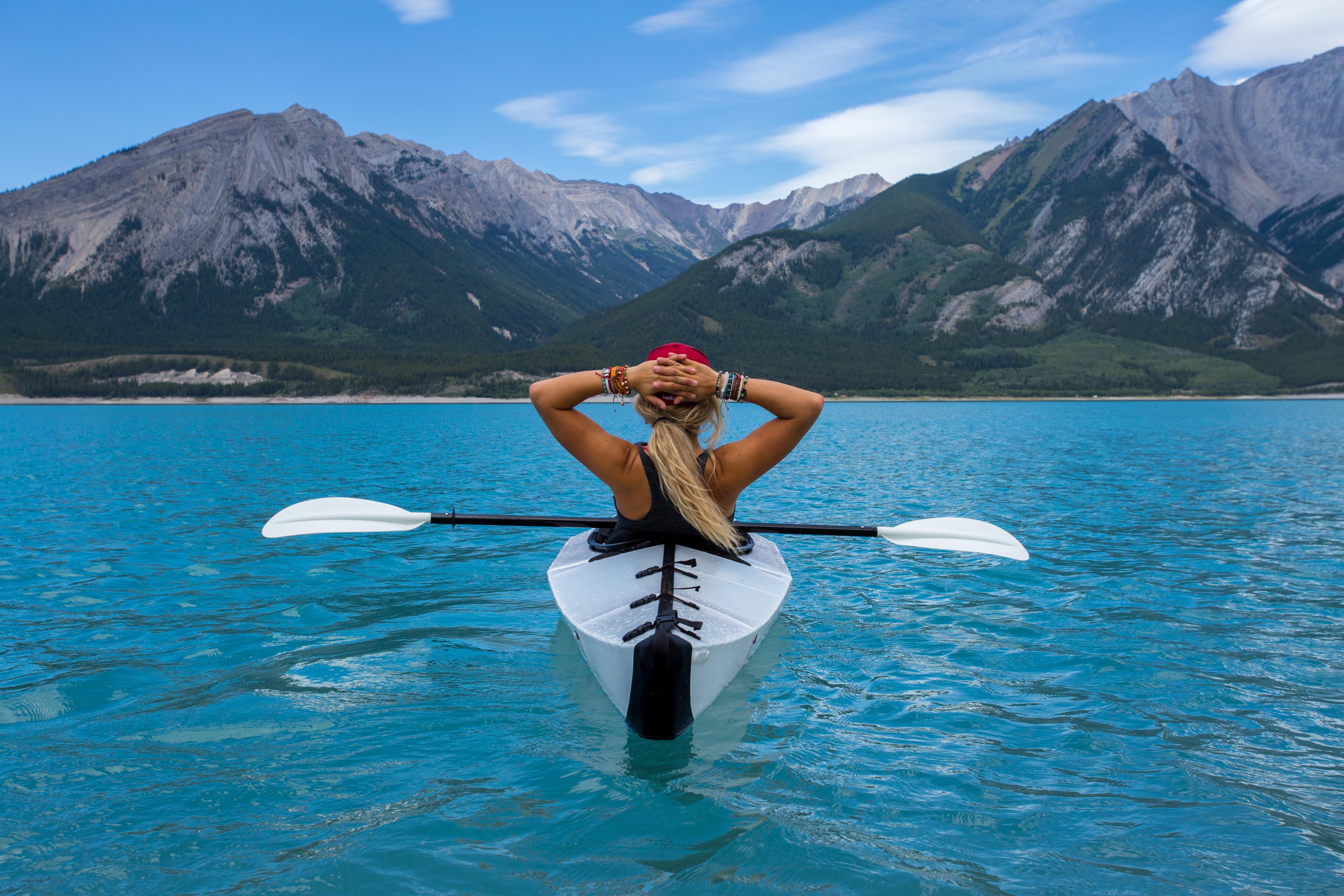 Woman relaxing in a kayak in a mountain lake