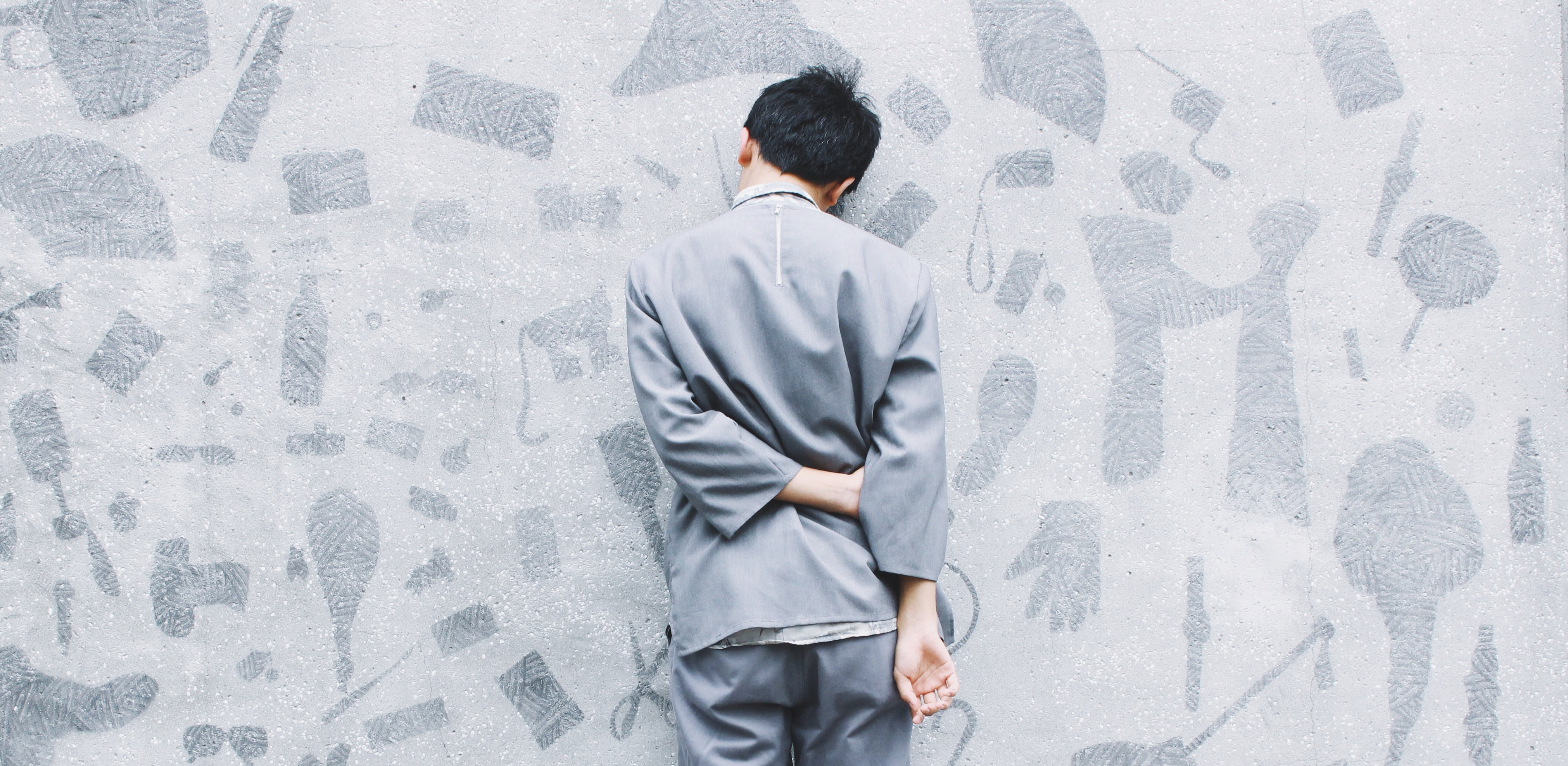 Adult standing against a wall, in timeout